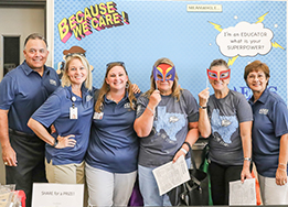 EMS employees take a group photo at the Education Foundation's superhero photo booth.
