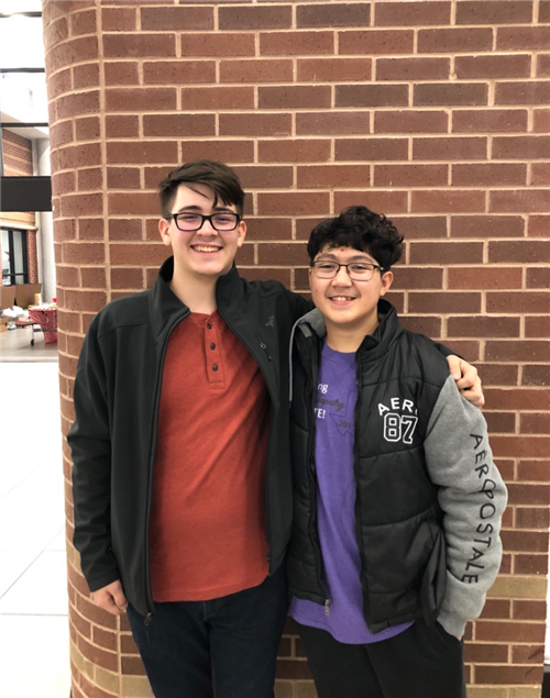 Chisholm Trail band students Ben Simmons and Christian Lackey pose for a picture in the hallway.