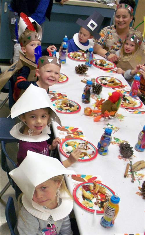 Children in the Employee Child Care program eat pie at their Thanksgiving celebration.