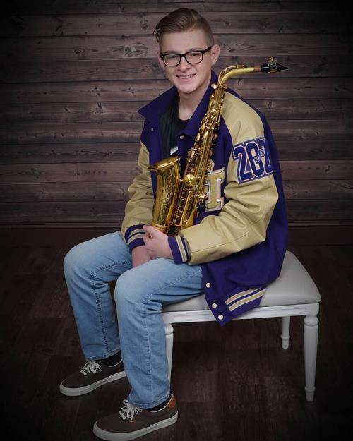 Chisholm Trail student Coleman Kading poses for a picture wearing a letteman jacket and holding his saxophone.