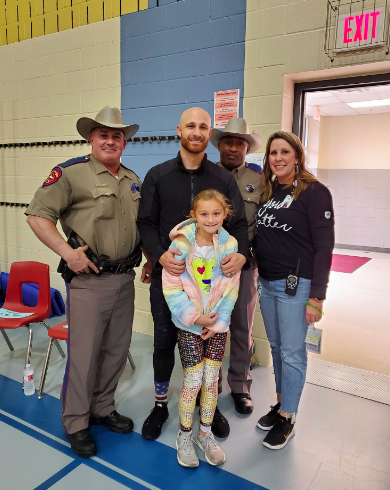 Jonathan Lucroy poses with police officers, a student, and staff member in the school's gym.