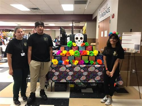 Saginaw HS Spanish students and teacher pose in front of their face painting booth at Taste of Northwest.