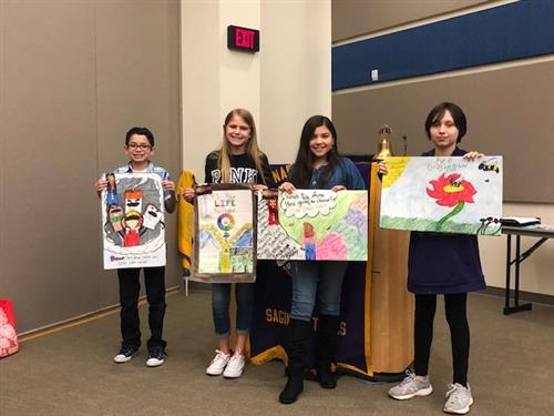 Students Juan Berry, Bailey Hansen, Emily Alvarez, and Danica Krumland hold up their posters at the Lions Club meeting.