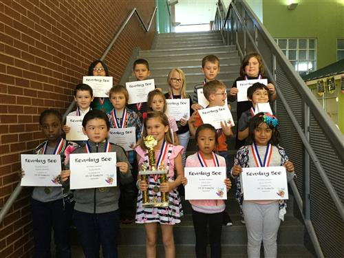 District Reading Bee competitors pose for a group picture with the Champion, Sophie Alonzo, in the center.