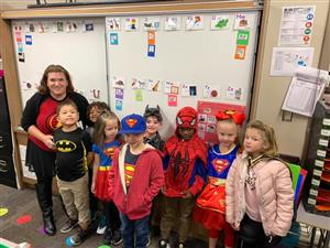 Dozier students pose for a picture with their teacher while wearing their Superhero costumes.