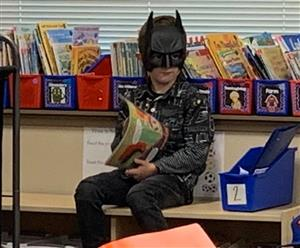A Dozier student reads a book in class while wearing his Batman costume.