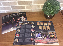 EMS Proud magazines stacked on table with one copy open to EMS Proud coverage page beside a plant.