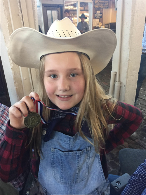 Ella Van De Kieft poses with her finalist medal at the Red Steagall Cowboy Gathering Children's Poetry contest.