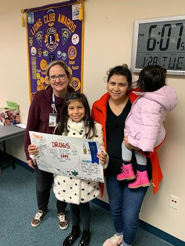 Frida Reyes poses with her family and art teacher while holding her winning poster.