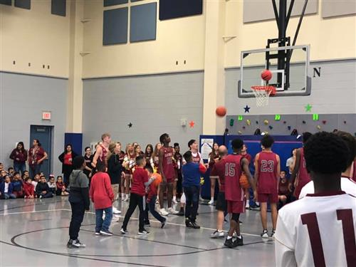 Saginaw HS basketball players run a basketball shooting contest with Gililland Elementary students in the gym.
