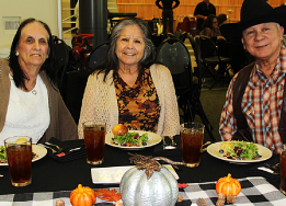 3 seniors sit at fall holiday decorated lunch table