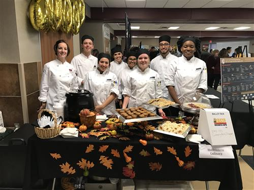 Culinary art students and Chef Natale pose at their table at Taste of Northwest.