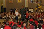 Military man in flight suit speaks to elementary kids in a gym