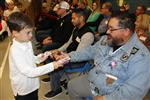 young boys hands a bookmark to veteran