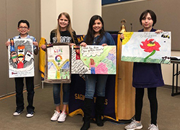 Students Juan Berry, Bailey Hansen, Emily Alvarez, and Danica Krumland hold up their posters at the