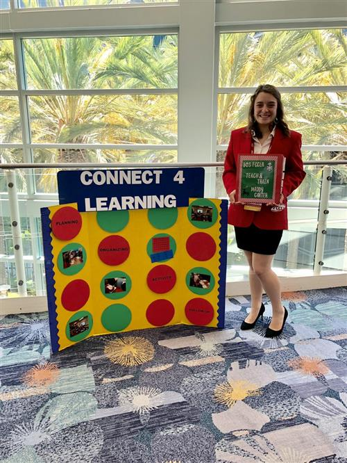 Maddy Carter poses at the national FCCLA competition with her project, Connect 4 Learning.