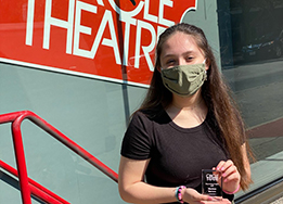 Madisen Berrera wears a face masks and poses with her trophy outside of Circle Theatre.