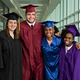 High school Profile of a Graduate committee members pose for a picture in graduation gowns.