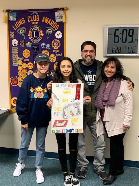 Sara Batista poses with her family and art teacher while holding her winning poster.