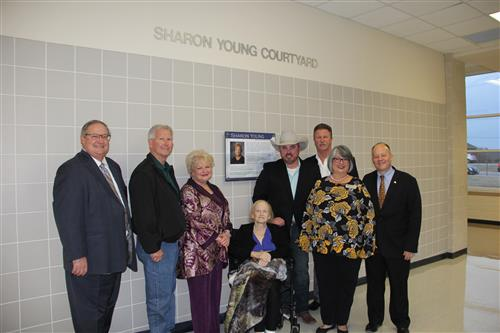 Sharon Young and her son Michael pose in front of her dedication plaque with the Board of Education Trustees.