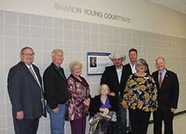 Sharon Young and her son Michael pose in front of her dedication plaque with the School Board.