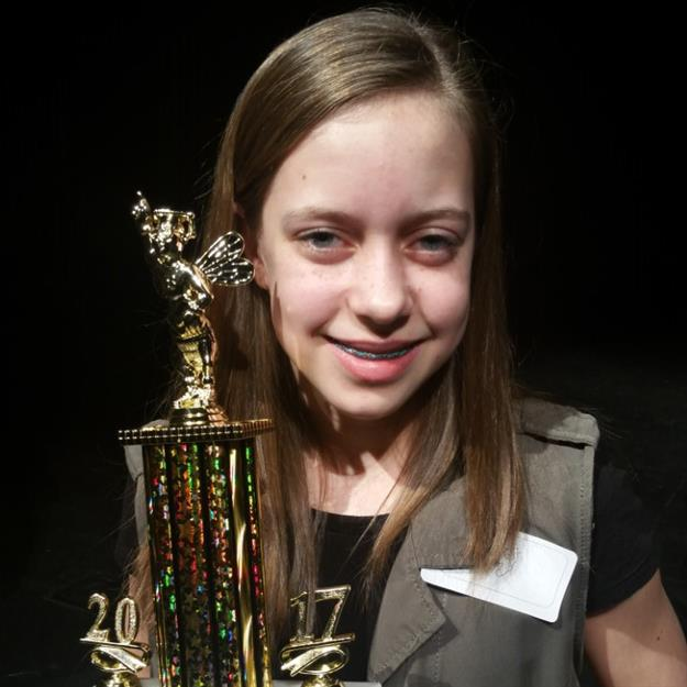 Kayli Jones posing with her area spelling bee trophy
