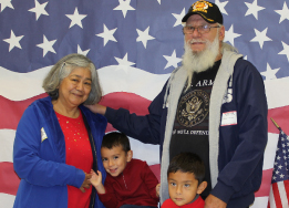 Veteran with his wife and two young boys in front of American flag