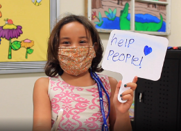 Photo of elementary student holding a sign that says help people