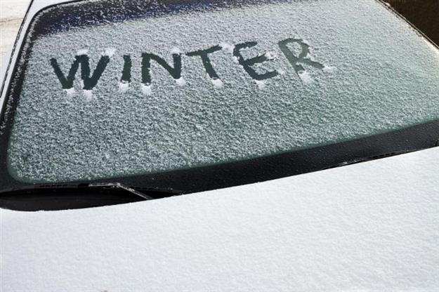 Image of car windshield covered in snow with the word winter written on it