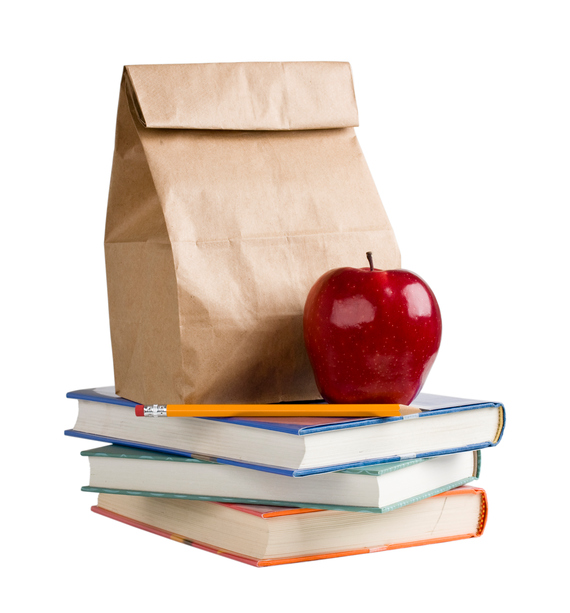 Photo of paper bag with apple on top of books