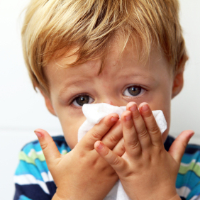 Stock image of a little kid blowing his nose.