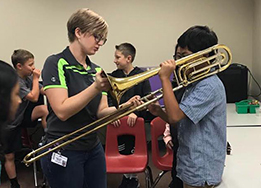 Prairie Vista Band Director Marquerite Bartek helps an elementary student try out the trombone.