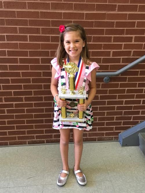 Saginaw ES student Sophie Alonzo poses with her District Reading Bee Champion trophy.