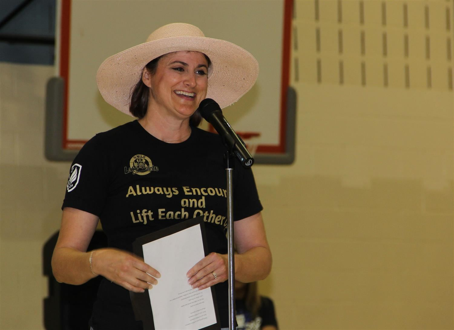 Staff member wears a hat and smiles in front of a microphone