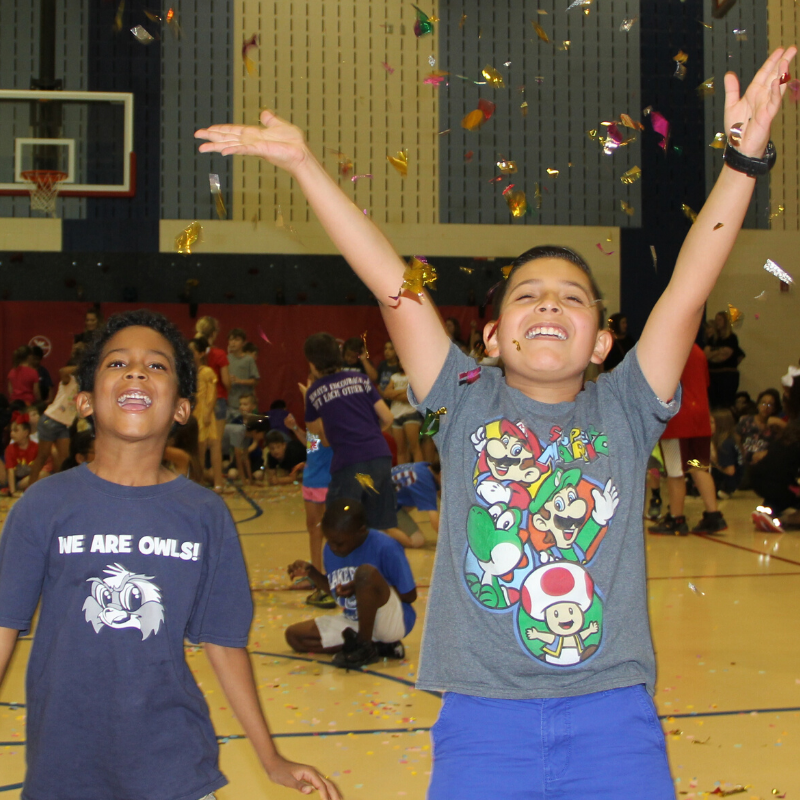 Students celebrate with confetti in a gym