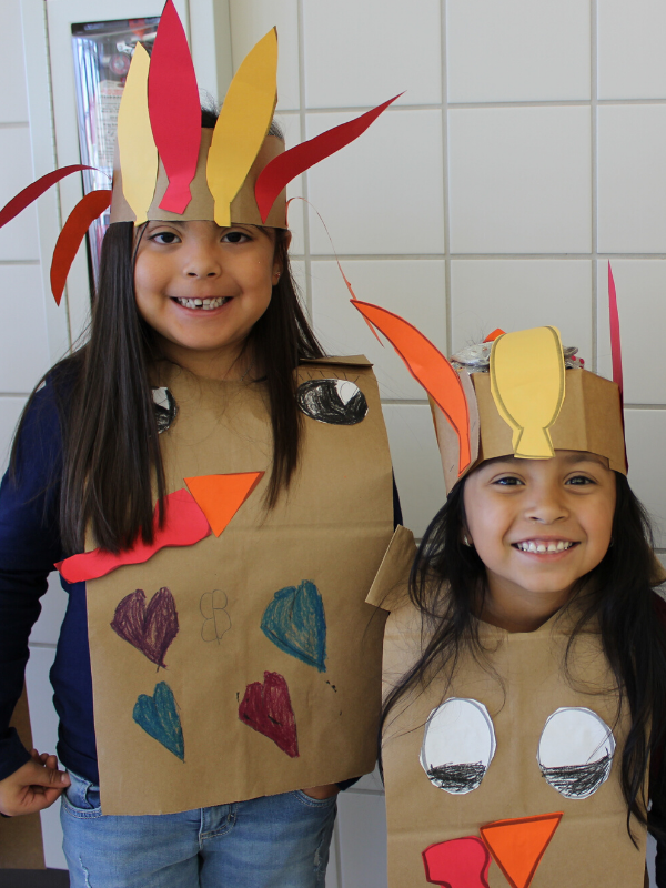 Students smile and wear turkey costumes