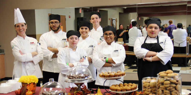 Culinary arts students standing with their arms crossed behind a table of food