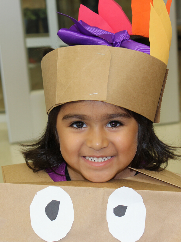Student wears a turkey headdress and smiles